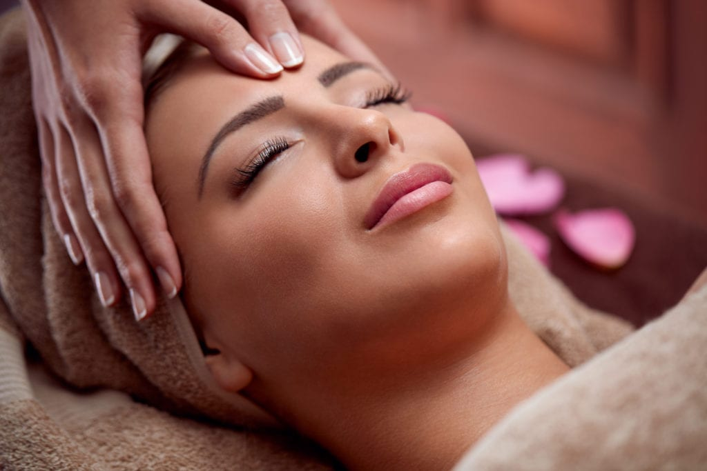 woman enjoy in face massage in spa salon