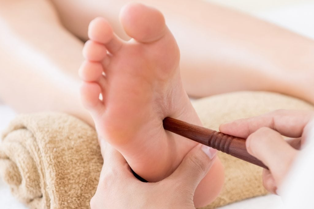 Professional therapist giving traditional thai foot massage with stick - panoramic banner
